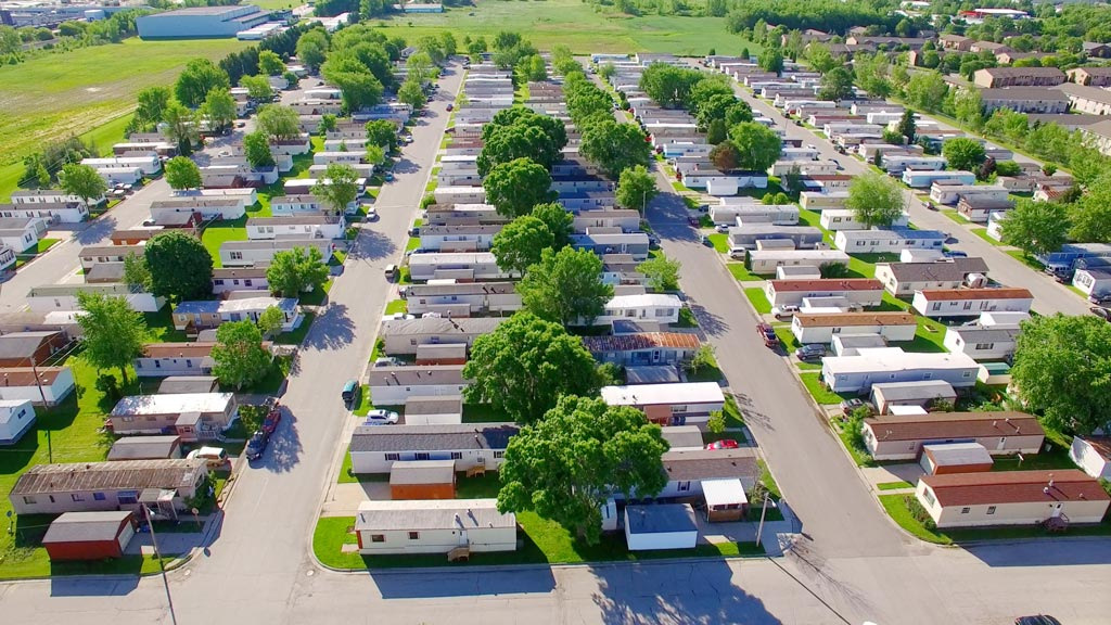 Vast trailer park, mobile home court on sunny summer morning, aerial view.